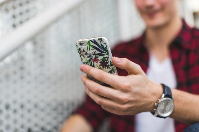 muž držící mobil s květovaným krytem