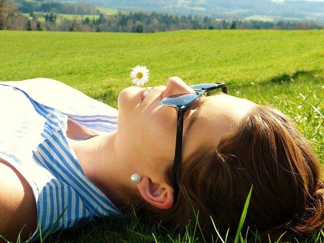 slunící se žena v trávě